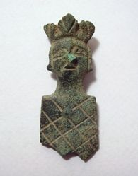 An incomplete copper-alloy two-piece trapezoidal strap-end with a three-dimensional anthropomorphic terminal in the form of a crowned male head.  The front of the strap-end is cast, decorated with incised cross-hatching, and has a recess in the back to accommodate the strap. The back plate, which is also incomplete, is of thin sheet metal, and was soldered in position. The single copper-alloy retaining rivet survives intact.   The generally similar MoL example referenced below was recovered…