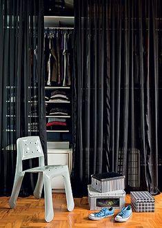O arquiteto Diogo Oliva montou seu guarda-roupa com araras metálicas e gaveteiros do ex-apartamento. No lugar de portas, pôs a cortina de voile preto. Os sapatos ficam guardados em caixas estilosas e a cadeira dá apoio na hora de se vestir, com o mesmo conforto de um closet.
