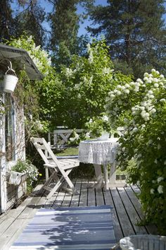 HVITE BLOMSTER: Det kan være utrolig effektivt å plante blomster i samme farge i samme hjørne av hagen. Det er en enkel måte å skape sammenheng på. Her har eierne laget en hyggelig sitteplass på utsiden av lysthuset også, og en flott syrinbusk pynter opp.