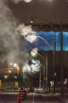 Tim Knowles - Dispersal Zone, 10 Existing street lamps modified with mixed media and smoke machines,  Toronto, 2015. Queens Quay East street lights are extinguished except for 10 modified lamps from which smoke billows.  Dispersal Zone changes dramatically hour by hour with the ever-shifting weather, the smoke drifting off in a plume, plunging and swirling on the wind or hanging illuminated in traffic lights this constantly shift work traces out the wind.