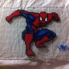 Spiderman perler beads by thepikashop Fuse Beads, Pearler Beads, Hama Beads Patterns, Beading Patterns, Spiderman Craft, Plastic Beads Melted, Marvel Cross Stitch, Pixel Art Grid, Iron Man