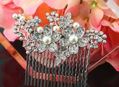 "Bridal Hair Comb Wedding Hair Comb Crystal by goddessdesignsgems, $48.00 ""Stunning"" this amazingly beautiful bridal comb features a gorgeous vintage style Austrian Crystal focal piece. This comb has a very pretty unique flower & leaf design with lustrous white pearls encrusted with dazzling crystals. Comb is Rhodium plated and affixed to a silver plated comb. The focal piece measures approx 2 1/2"" in length. This bridal comb is really fabulous!"