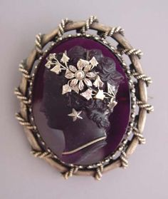 cameo amethyst-purple glass cameo brooch with silver twist setting and leaves and pearl tiara décor in hair, star earrings and a simple necklace