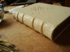 Bound in durable white calf leather, hand sewn on four hemp cords and with double core silk endbands, this large blank grimoire could be the perfect safeguard of your most treasured writings. The all gold decoration is a representation of nature and tradition. A true temple for your writings.  This book is 21x16 cm bound in white calf leather. It has about 600 pages blank unlined paper consisting of 60% recycled paper, 30% cellulose fibers and 10% cotton fibers. A special adhesive is used…