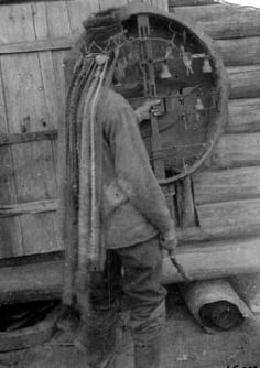 Photo of a Siberian shaman revealing the spirit figures, bells and charms inside of his very large drum.