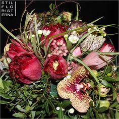 Närbild på droppformad brudbukett i vinrött, med fransiga tulpaner, fritillaria och orkidéer.