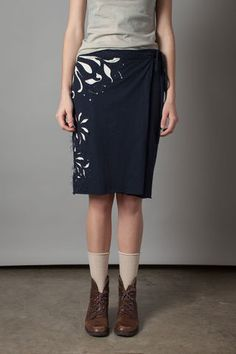 """This 100% organic medium-weight cotton jersey skirt wraps around the body and ties at the waist. Our Magdalena stencil is hand embroidered in placement fashion using reverse appliqué. Measures 24"""" in length. Shown here in Navy with Natural. Bottom layer comes in Natural. Choose your top layer color below.Please allow four to six weeks for delivery. Wash gently + Hang to dry. Free shipping. Made in the USA."""