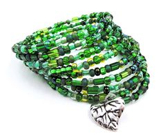 This rich emerald 9 row wrap bracelet is made on silver memory wire with a mixture of gorgeous grassy green glass Czech beads and a silver leaf charm to top it off. ★ Return to my main shop page here for more inventory ★ www.etsy.com/shop/bridgetollbeading ★ Read my FAQs below and if you have any further questions please do not hesitate to contact me! ★ https://www.etsy.com/shop/BridgeTollBeading?ref=hdr#more-section