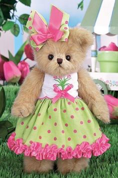 """Becca Blooming is 10"""" in height. She is wearing a green bow with rose colored dots with a rose bow on top of it. Her top part of the dress is white. In the m"""