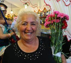 Maria Jesús (de las Flores), selling carnations, Caseta Los Nietos de Don Manuel, Feria de Sevilla, April 14, 2016.  Mari Carmen has a different dress and differnet shawl for every day of the Feria.  Photo by Gerry Dawes©2016, Canon M3