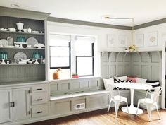 Gorgeous gray dining room banquette plus built-in hutch. The paneled board and batten below the ledge is gorgeous above the banquette!