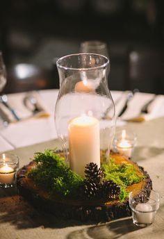 Elegant candles in hurricane glasses, moss, pinecones // Julie Wilhite Photography