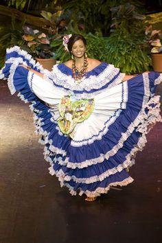 Este es un vestido tradicional de Honduras. El vestido es blanco y azul. La chica lleva collares interesantes. Hay flores rosados en su pelo.