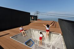 with an emphasis on promoting creativity and movement, the kindergarten in japan integrates a netted climbing structure, giving the children access to a rooftop terrace overlooking the ocean.