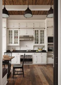 Love the wood and white cabinets with a few glass fronts. So pretty!