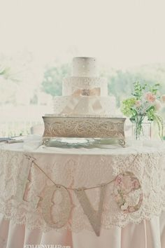 Wedding cake table with lace overlay and LOVE banner, which could be made from paper.