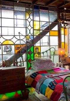 I would love to sleep in front of a stained glass wall...sort of industrial Boho.