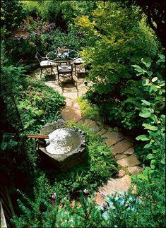 Curving flagstones lead to a dining terrace tucked into a sloped garden. T… – backyard design ideas Forest Garden, Woodland Garden, Garden Stones, Garden Paths, Hill Garden, Lush Garden, Small Gardens, Outdoor Gardens, Courtyard Gardens
