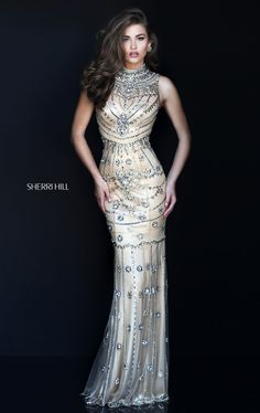 Project an aura of rich sensuality in the Sherri Hill 50239 sleeveless prom dress. This lustrous jersey gown cleaves to the curves sensationally. An elaborately beaded high illusion neckline tops the sweetheart bodice with slightly curved waistline, and is arrayed with glittering jewels. An intricate beaded design adorns the full illusion back. Shimmering beads adorn the skirt as it flows smoothly into a floor-length, delicately beaded hemline.