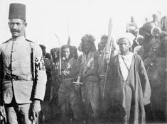 Anglo-Sudan War, 1898-99: A group of Hadendowah Sudanese bearing weapons at Berber. An Egyptian military policeman stands in the foreground. Mahdi forces evacuated Berber after their defeat at Abu Hamed. Lord Kitchener's forces occupied the town on August 31 1897. These men may have been left behind by the Mahdi.