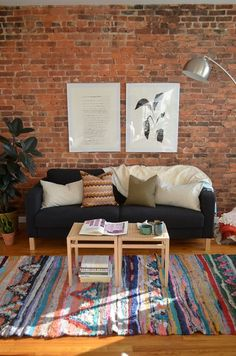 Cozy sofa, colorful rug and exposed brick wall - living room decor