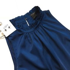"""NWOT Ann Taylor Sleeveless Blouse Gorgeous high neck blouse with pleating/ruffle details around neck.  Beautiful deep blue color that I'm not too sure on how to describe.  Back has a peephole neck button closure. Excellent new condition! I noticed a tiny line in the lower back of the shirt shown in pic.  Not quite a snag but wanted to be sure to show in pic.  True color of top is in 1st 2 pics - 97% Polyester 3% Spandex   Simple yet elegant!  Measurements: Laying flat 26"""" length from top of…"""