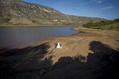 os noivos caminhando na praia do lago da lapinha da serra uma vista ampla