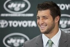 New York Jets quarterback Tim Tebow reacts as he answers a question while he is introduced at a New York Jets news conference at the team's training center in Florham Park, New Jersey March 26, 2012. Tebow was traded to the Jets from the Denver Broncos last week.