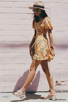A woven mini wrap dress featuring an allover floral print, short puff sleeves, a self-tie waist, and a surplice neckline.