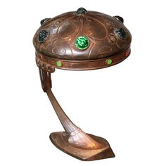 Copper Arts & Crafts Period Desk Lamp  Austria  1910  An Austrian copper Arts & Crafts period desk lamp with repousee texture and round half dome shade having inset textured glass paste stones and supported by triangular base supporting curved arm