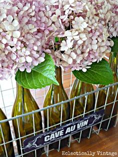 Hydrangea wine bottle centerpieces from Eclectically Vintage Blog. Not sure what the basket is about but really like the look of the hydrangeas in the bottles