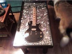 Guitar coffee table.  The background is broken CD pieces and the legs are from a bunkbed.  Awesome !