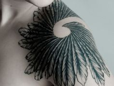 A stunning black and white tattoo of a spiral of feathers
