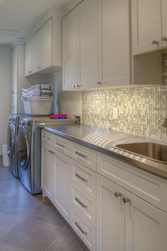 White cabinets are a timeless choice for a laundry room, ensuring the space will stand the test of time with a bright, fresh and clean look. Stainless steel countertops and a mosaic tile backsplash lend a stylish feel to this space.