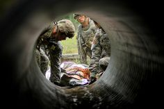 "A team of medics led by Cpl. Eric Smith, assigned to the 1st Squadron, 89th Cavalry Regiment, prepare to transport a ""casualty"" through a culvert during the best medic competition this week. The annual event pits candidates against one another to earn a chance to compete in a national competition held at Fort Sam Houston. Photo by Capt. Michael Greenberger"