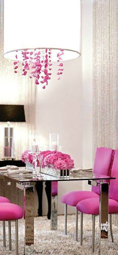 Glass Designed Table with pink chairs, and a chandelier with pink streamers