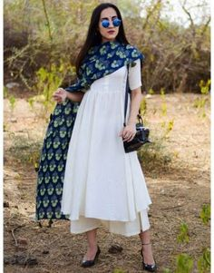 beautiful contrasts with the breezy white. The set includes a flowy kurta with a gorgeous ghera, a comfy short palazzo and a hand block printed dupatta. Match it with a pair of kolhapuris and you are ready with the perfect look this summer! Salwar Designs, Kurta Designs Women, Kurti Designs Party Wear, Short Kurti Designs, Blouse Designs, Indian Fashion Dresses, Dress Indian Style, Pakistani Dresses, Indian Fashion Modern
