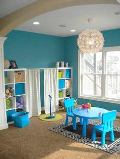 Une super idée pour la salle de jeux de vos enfants. Le rideau présent entre les deux étagères crée une petite « scène » de spectacle.