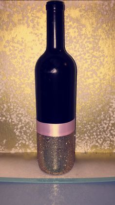 Wine Bottle that we Spray Painted Black. Before spray paint, the bottle was green. Gold glitter and pink ribbon.  Centerpieces
