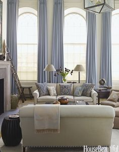 Grandly arched windows in the 18-foot-high living room of a Manhattan maisonette are framed by the icy blue of Holland & Sherry Glace curtains in Glacier. Christopher Maya designed the sofa and had throw pillows made from antique Fortuny Fabric.   - HouseBeautiful.com