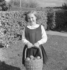 Photograph by Max Dupain of girl with basket of tomatoes at Hagley Farm School, Tasmania, 1946