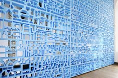 Over at a design museum in Utrecht, The Netherlands, Amsterdam-based design studio Rietveld Landscape has devised this pale blue wall divider that looks something like a monochromatic, stained glass cityscape.