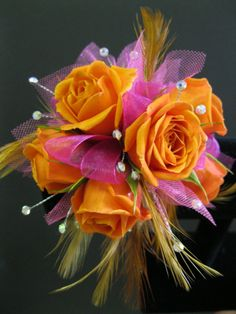 Corsage with orange spray roses, pink ribbon & accents and feathers