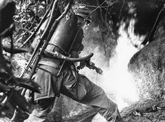 A trooper of the U.S. 1st cavalry division aims a flamethrower at the mouth of cave in An Lao Valley in South Vietnam, on April 14, 1967, after the Viet Cong group hiding in it were warned to emerge. (AP) ~ Vietnam War