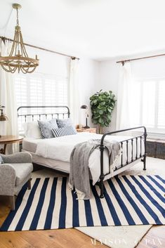 simple coastal master bedroom: get tips for casual blue and white bedroom decor! #bluewhitestripes #bedroomdecor #farmhousebedroom #ironbed #layeredrugs #bedroomdecoratingideas