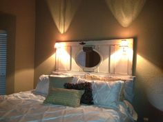 Headboard I made out of an old antique door , custom painted it and distressed it and added a antique mirror I painted and 2 antique wall sconce lights and a little sign , and donated for a fundraiser for a sweet little boy with cancer.  I try to give back when I can , and pediatric brain cancer doesn't receive enough funds like they should .  < this is my created headboard hanging in the ladies room that won the auction on it , she shared the photo after it was hung.
