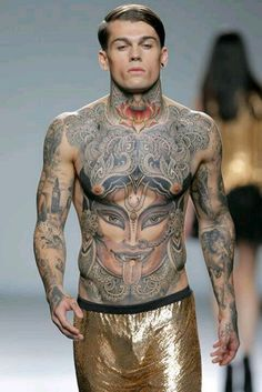 Male runway model with full body Buddhist / Hindu spiritual tattoos.