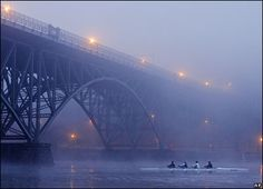 Rowers on the Schuylkill River pass the Strawberry Mansion Bridge on a foggy morning in the city of Philadelphia