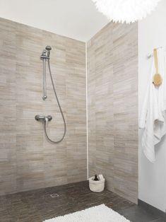 Inspiration brute dans cette douche à l'italienne parée d'un revêtement mural imitation marbre.