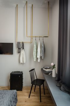 Custom brass clothes hangers, instead of a full closet, take up the empty space above the built-in shelf.